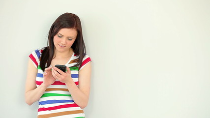 Happy young woman texting on her phone