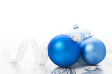 Blue xmas balls and silver ribbon on holiday background