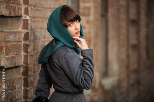 Sad young woman in grey classic coat at the wall
