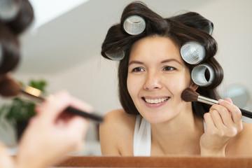 Woman in curlers applying makeup