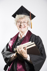 Elderly college graduate holding books