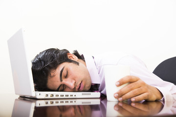 young indian business man sleeping on laptop