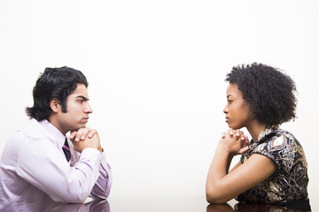 ethnic business man and woman stare at each other