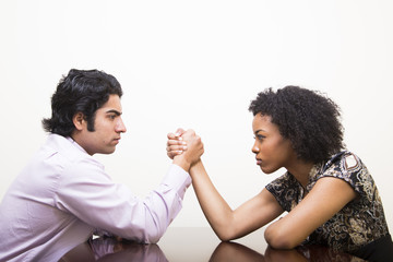 ethnic young business man and woman arm wrestle on desk