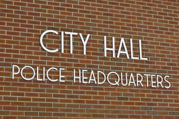City Hall & Police Headquarters Sign Against Brick Background