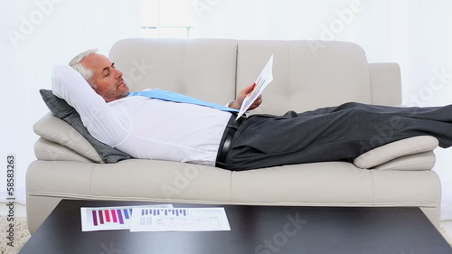 Businessman falling asleep holding paperwork on the couch
