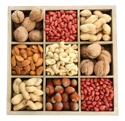 assortment of tasty nuts in  wooden box, isolated on white