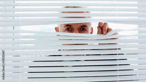 Businessman spying through blinds and getting caught by camera
