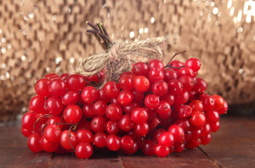Red berries of viburnum on table on brown background