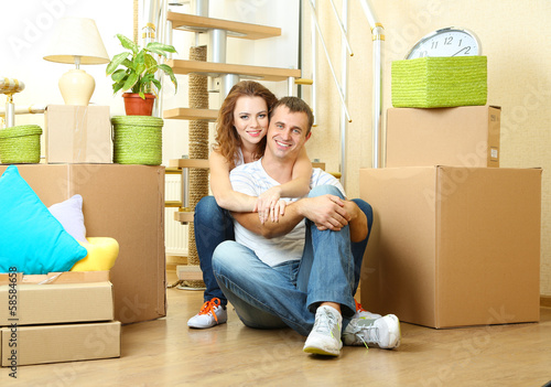 Young couple sitting in new house on staircase background