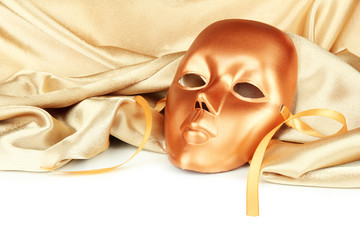 Mask on gold fabric on white background