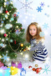 Little girl decorating Christmas tree with baubles in room
