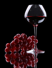 Wineglass with red wine, isolated on black