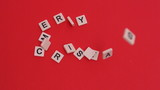 Letter tiles moving to spell merry christmas on red background