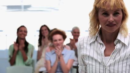 Businesswomen applauding colleague after presentation