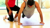 Fit toned man doing press-ups in fitness hall
