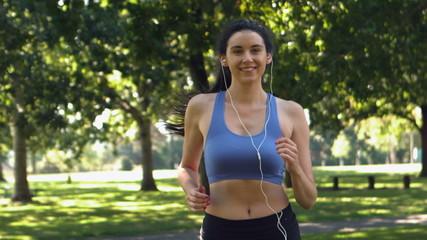 Happy brunette running in park