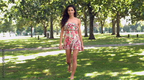Gorgeous happy brunette walking in park