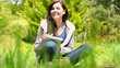 Happy young woman sitting on grass writing on notepad