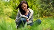 Smiling young woman sitting on grass writing on notepad