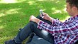 Handsome young student sitting on the grass texting