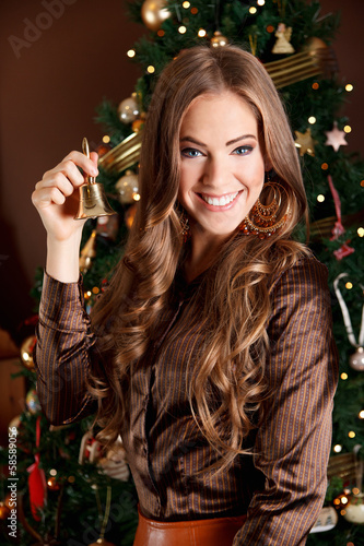 Beautiful young woman holding a bell at Christmas Eve