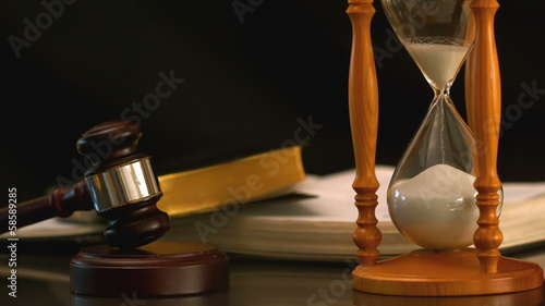 Sand flowing through hourglass beside gavel and bible