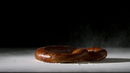 Pretzel falling onto flour on black background