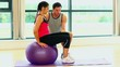 Pretty woman training sitting on fitness ball with coach