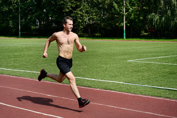 Athlete runner trains at the stadium