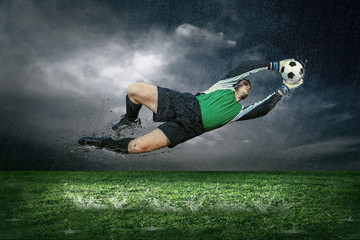Football player with ball in action under rain outdoors