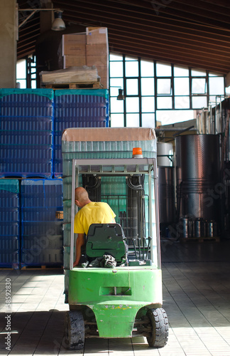 Warehouse worker loading wine boxes by forklift