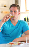 Man drinking glass of white wine.