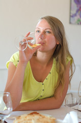 Woman is drinking glass of white wine