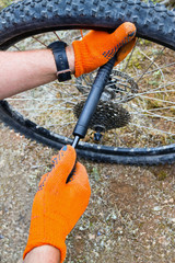 Bike maintenance pumping up tyre. Closeup of mechanic pumping