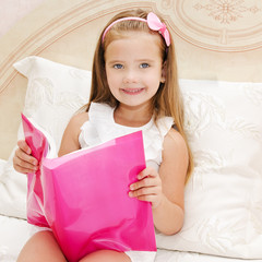 Cute little girl reading a book on the bed