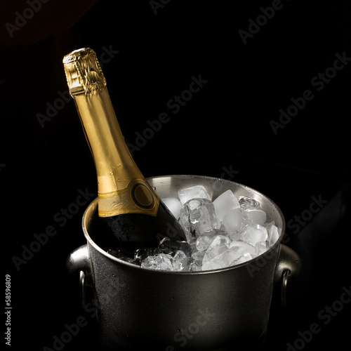 bottle of champagne in an ice bucket on a black background