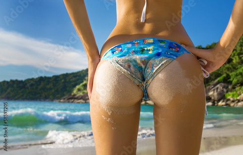 Sexy sandy woman buttocks on the beach background