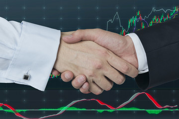 Handshake over stock market graph.
