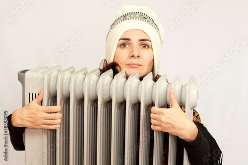 Young woman holding an electric  heater