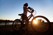 silhouette of young woman with bicycle outdoor