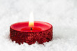 Red sparlky tealight on snow background