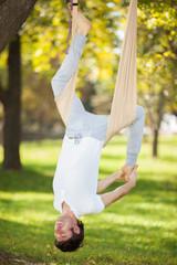Anti-gravity Yoga, man doing yoga exercises in the park