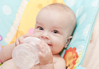 happy baby holding bottle
