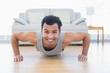 Sporty smiling man doing push ups in the living room