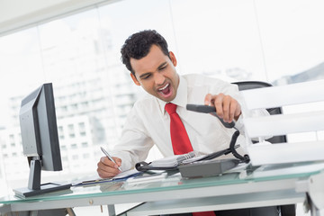 Businessman shouting as he holds phone at office
