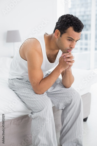 Thoughtful young man sitting on bed