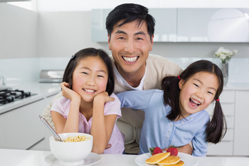Smiling man with happy daughters having breakfast in kitchen