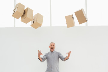 Annoyed mature man with falling boxes