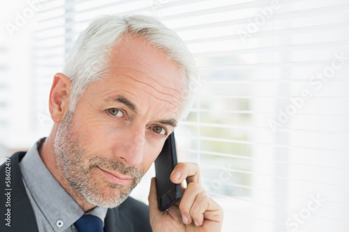 Close-up of a serious mature businessman using cellphone